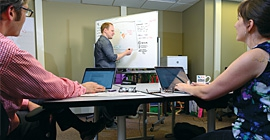 Two people work on laptops while a person writes on a white board