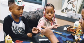 Two young children listen to a teacher in a classroom